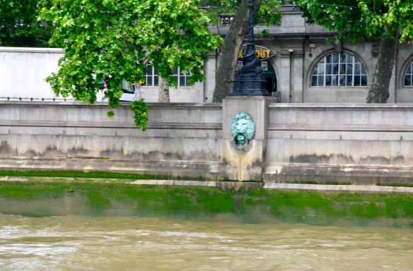 Bronze lion heads line the wall of the River Thames, London.