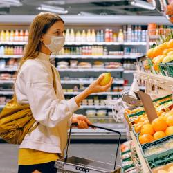 Girl wearing coronavirus mask shopping at grocery store