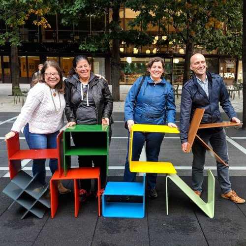 """Glenda Sims, Estelle Weyl, Janet Swisher and Adrian Roselli pose along with metal letter-shaped chairs spelling """"HACK"""" and """"MdN"""""""