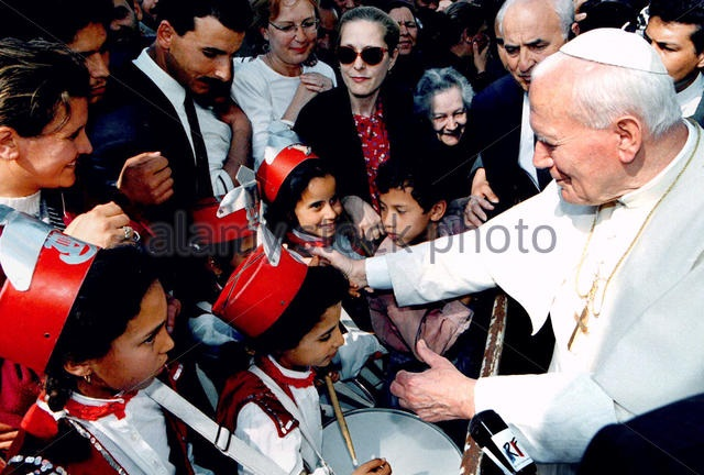 Pope Jean Paul II greets Tunisian Moslem children who arrived at the Catholic cathederal to welcome him April 14. The Pope is on his first trip to this mainly Islamic country with about 15,000 Catholics