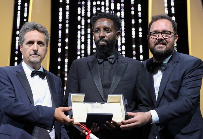 Ladj Ly (au centre) reçoit le Prix du Jury pour Les Misérables, ex-aequo avec les brésiliens Juliano Dormelles et Kleber Mendonça pour Bacurau VALERY HACHE / AFP