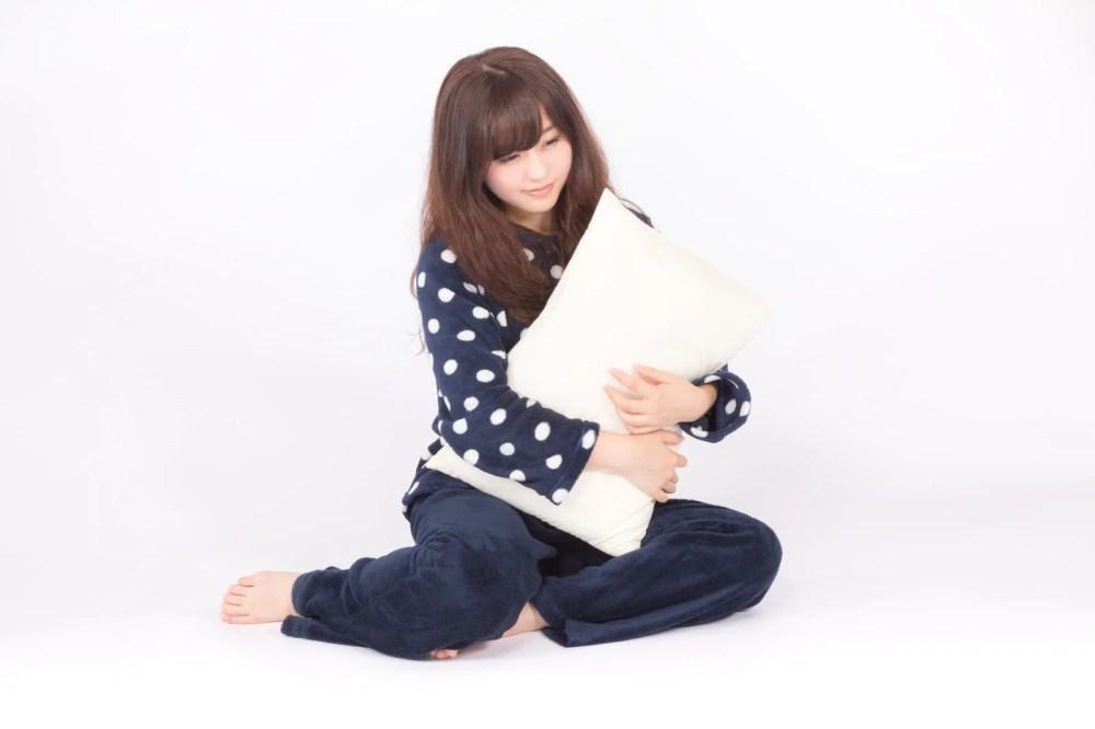 枕を抱いて眠そうな表情の若いパジャマ姿の女性