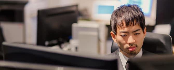 PCが並ぶオフィスでモニタリングする男性