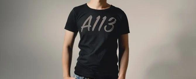 A113と書かれたTシャツを着てポージングする男性
