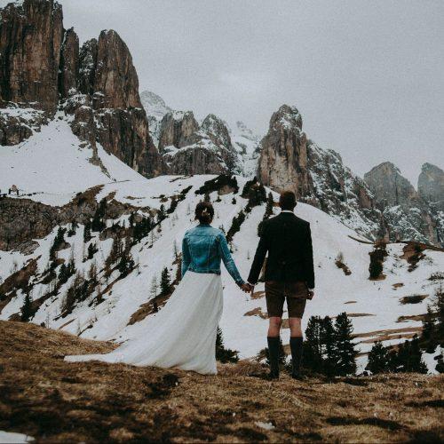 Sposi guardano le montagne innevate tenendosi per mano Alta Badia Dolomiti Italia Trentino Alto Adige