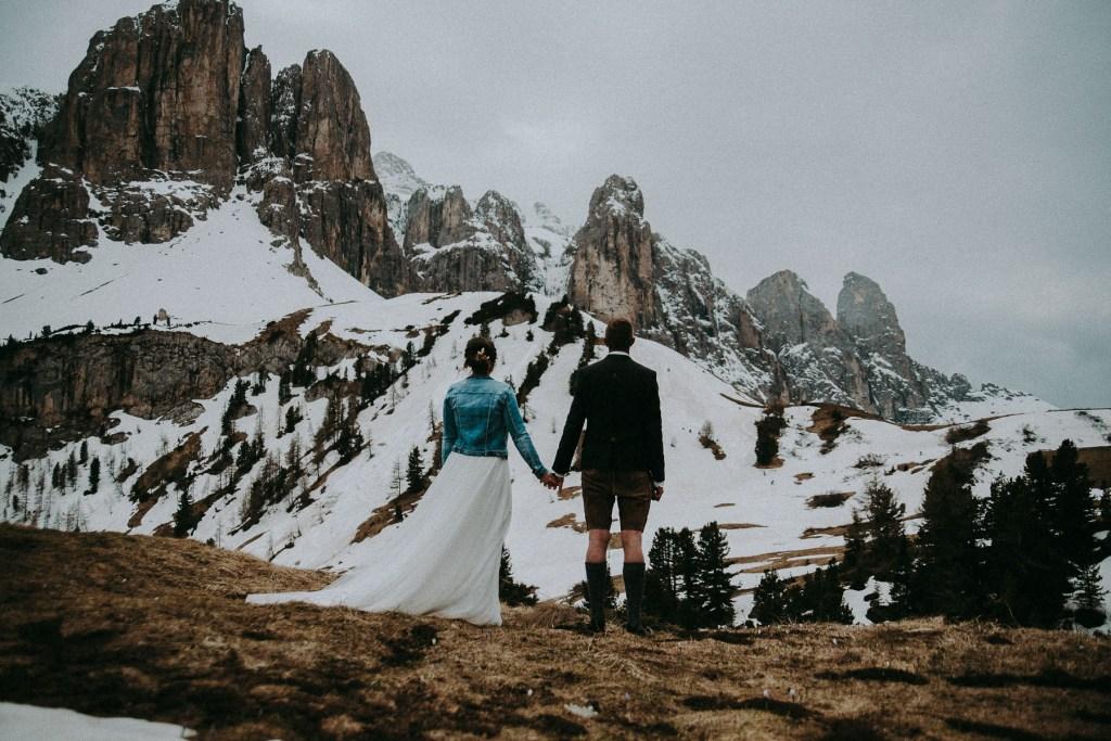 Hochzeitspaar mit Blick auf die verschneiten Berge und Händchen haltend Alta Badia Dolomiten Südtirol Italien