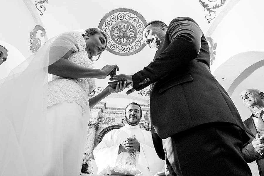 Bride placing ring onto grooms fingers in an Italian wedding