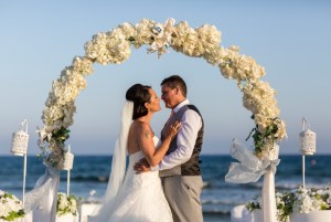 Vow renewal couple by the beach under arch