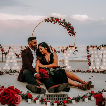 Adorned with scarlet roses and LED lights by the crashing waves, this wedding proposal exuded magical vibes