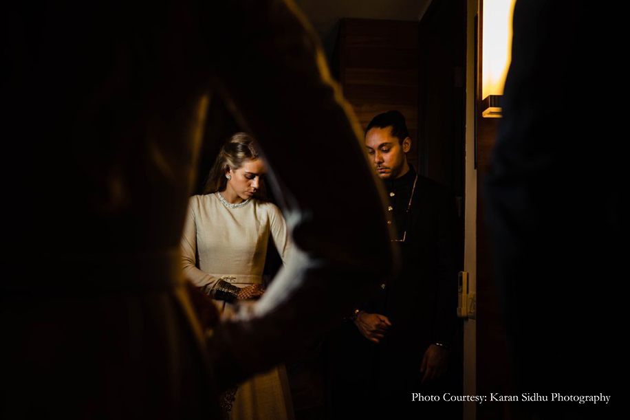 Bride in Cream Sabyasachi gown for cocktail and groom in black bandh gala