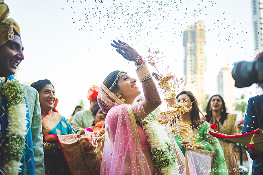 Bride wearing onion pink lehenga by Neeta Lulla with gold motifs, pearls, and sequins work