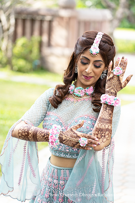 Bride in a teal blue and pink lehenga with floral jewelry for her mehendi