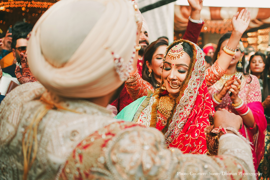 Bride wearing Rajasthani embroidery red and turquoise lehenga and groom in Off-white sherwani with an elaborate Kalgi and Mala at anand karaj