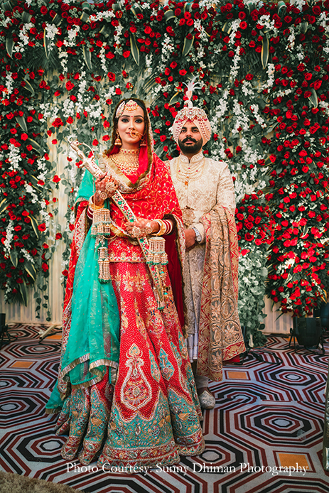 Bride wearing Rajasthani embroidery red and turquoise lehenga and groom in Off-white sherwani with an elaborate Kalgi and Mala