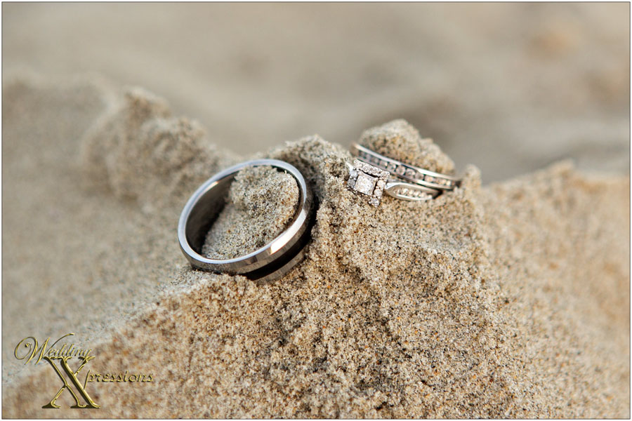 wedding rings on sand at the beach