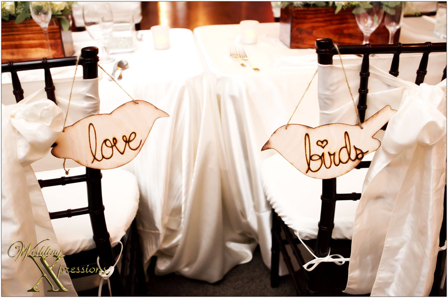 love birds sign at wedding head table