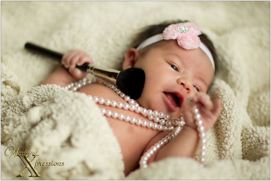newborn with pearls and makeup