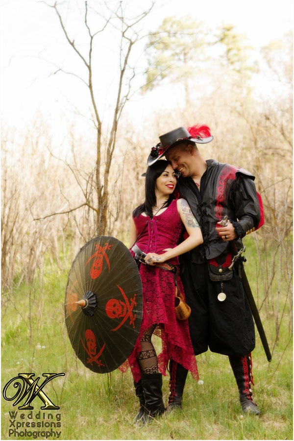 renaissance engaged couple in black and red outfit with umbrella and sword