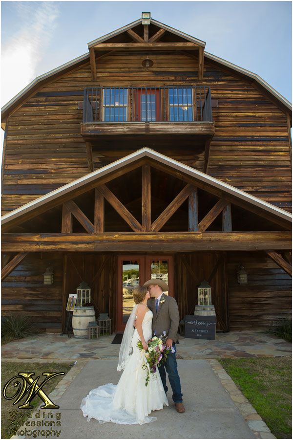 wedding couple kissing in front of Thistle Springs Ranch