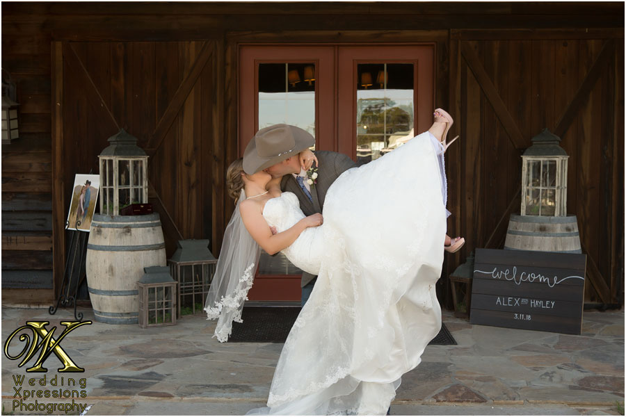 groom carrying bride in front of Thistle Springs Ranch
