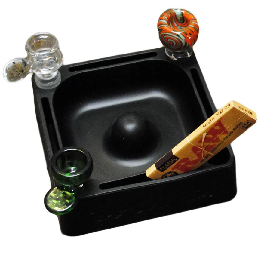 Tap Dat Ash is a soft rubber ashtray that protects glass pipes, with slots for rolling papers and smoking accessories