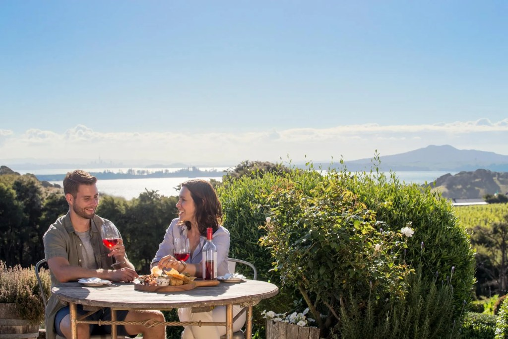 Couple eating and drinking on Waiheke Island with Auckland city and Rangitoto Island in the background