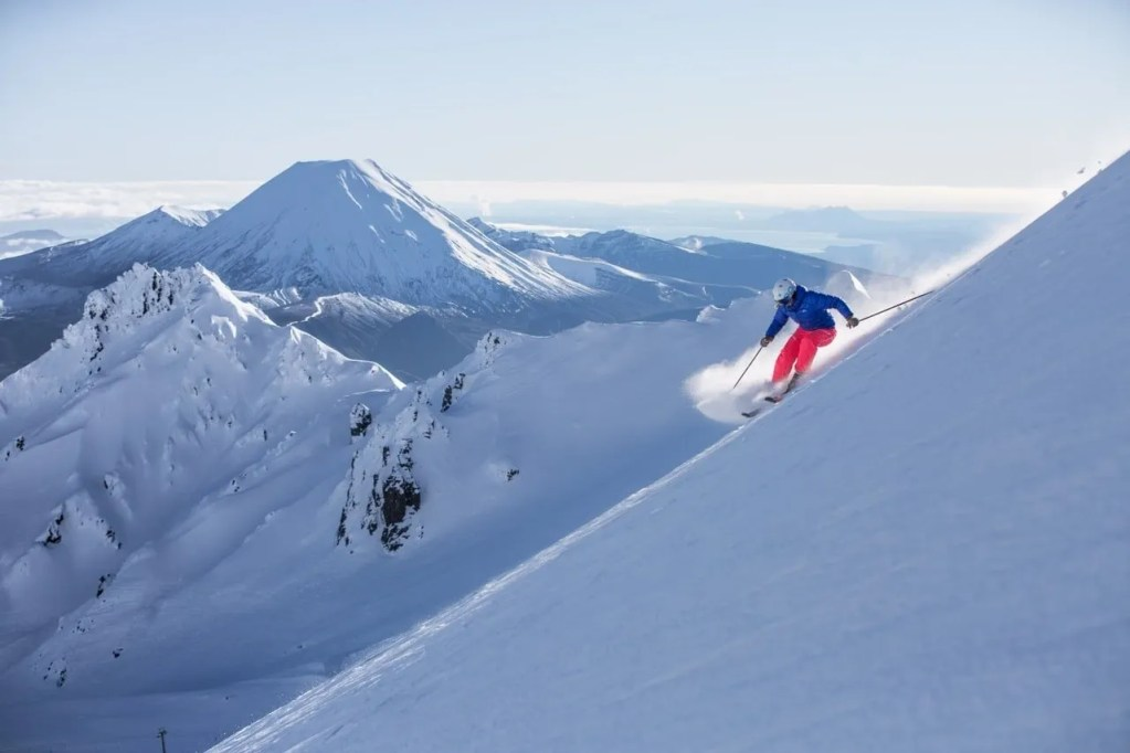 skier with pink pants and blue jacket skiing in whakapapa ski field in front of mt ngauruhoe