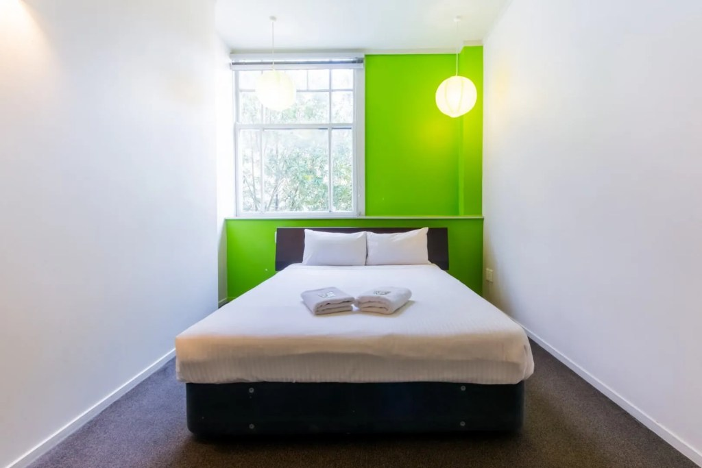 Room with double bed, a window and a green wall at jucy snooze auckland