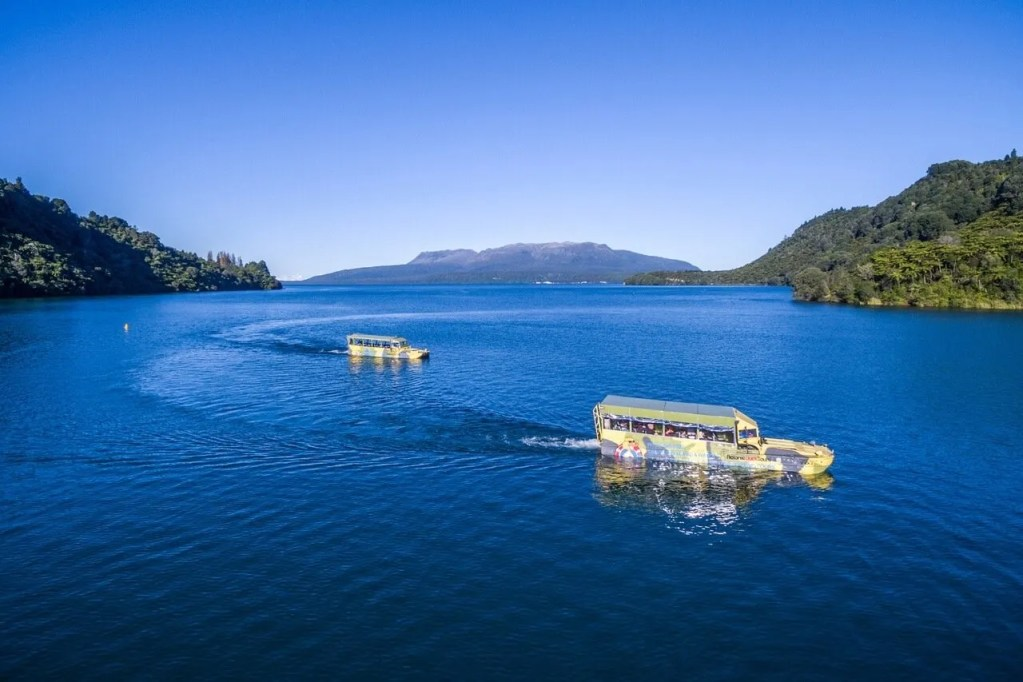 Two rotorua duck tours vehicles cruising on lake tarawera on a sunny day, mt tarawera in the background