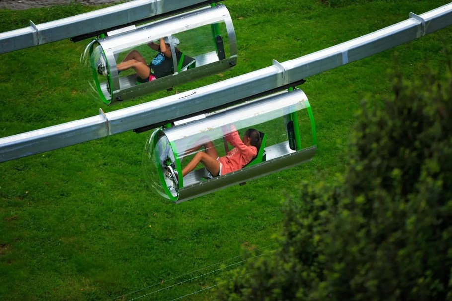 Two kids racing against each other in the Shweeb Racer pod in Velocity Valley Rotorua New Zealand