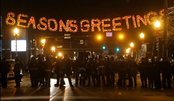 Not photoshopped. Police gather under holiday sign in Ferguson tonight.
