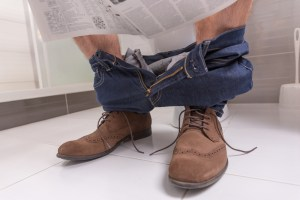 man sitting on toilet reading newspaper