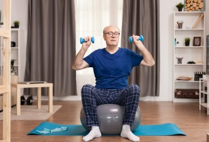 senior man lifting weights in living room
