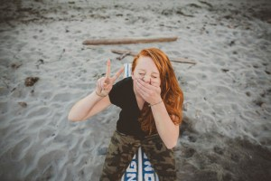 Portrait of redhead teenage girl sitting at the beach being goof