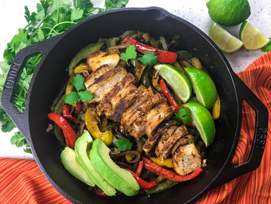 Chicken Fajitas and vegetables in a cast iron skillet