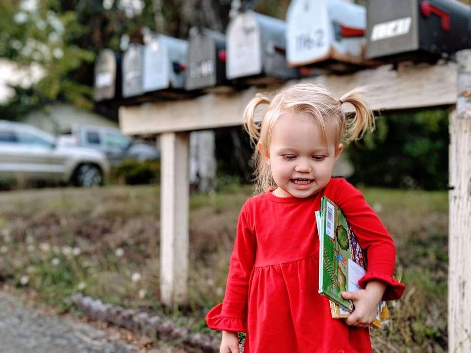 little girl holds childrens library books