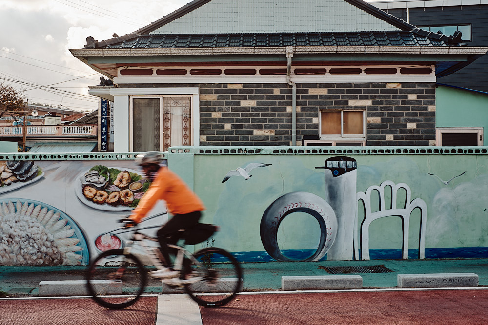 A Rider Passes by a Mural of the Baseball Bat Lighthouse