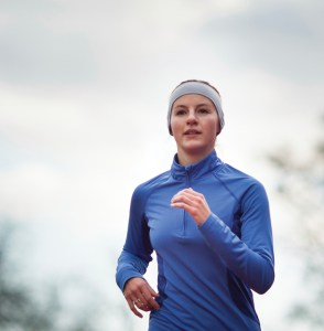 Portrait of a woman running against against blue sky