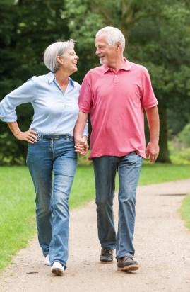A senior couple holding hands walking in the park