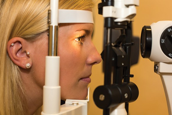 A female patient getting her eyes checked with a slit lamp