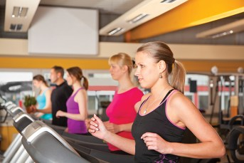 group of five people exercising in gym running on treadmills