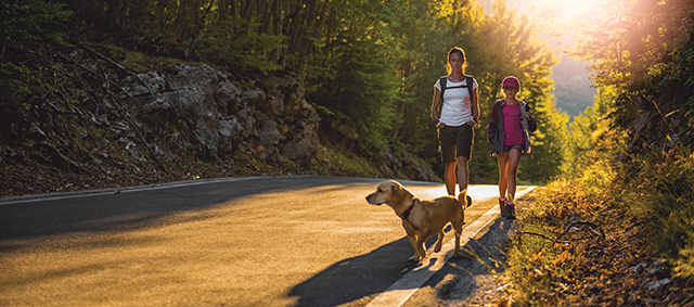 Mother and daughter Hiking by the asphalt road