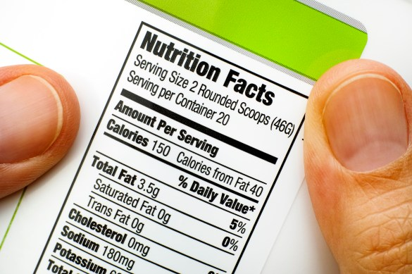 Woman fingers with protein jar. Reading nutrition facts