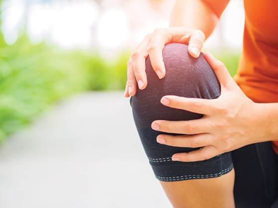 Runner sport knee injury. Woman in pain while running in the garden.