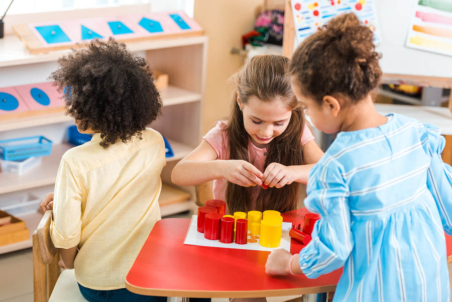 Children Playing Colorful Educational Game At Desk In Montessori