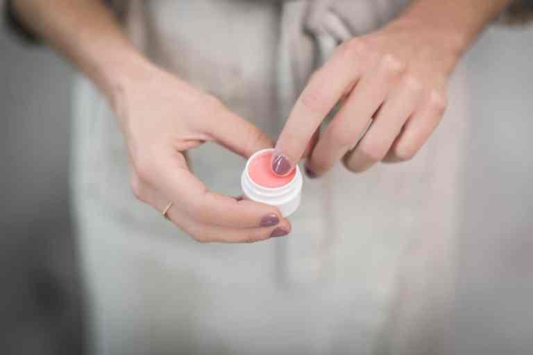 Frau nimmt mit Finger Creme aus Tiegel