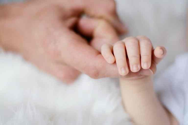 Babyhand umklammert Finger
