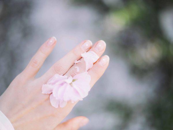Hand mit Blumenblättern