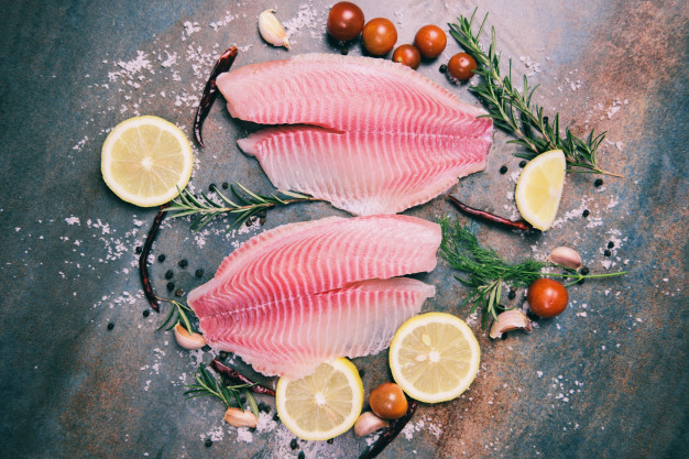 fresh-fish-fillet-sliced-steak-salad-with-herbs-spices-rosemary-tomato-lemon-raw-tilapia-fillet-fish-salt-dark-stone-background-ingredients-cooking-food_73523-3271