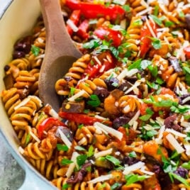 Creamy eggplant pasta with a wooden spoon in a skillet